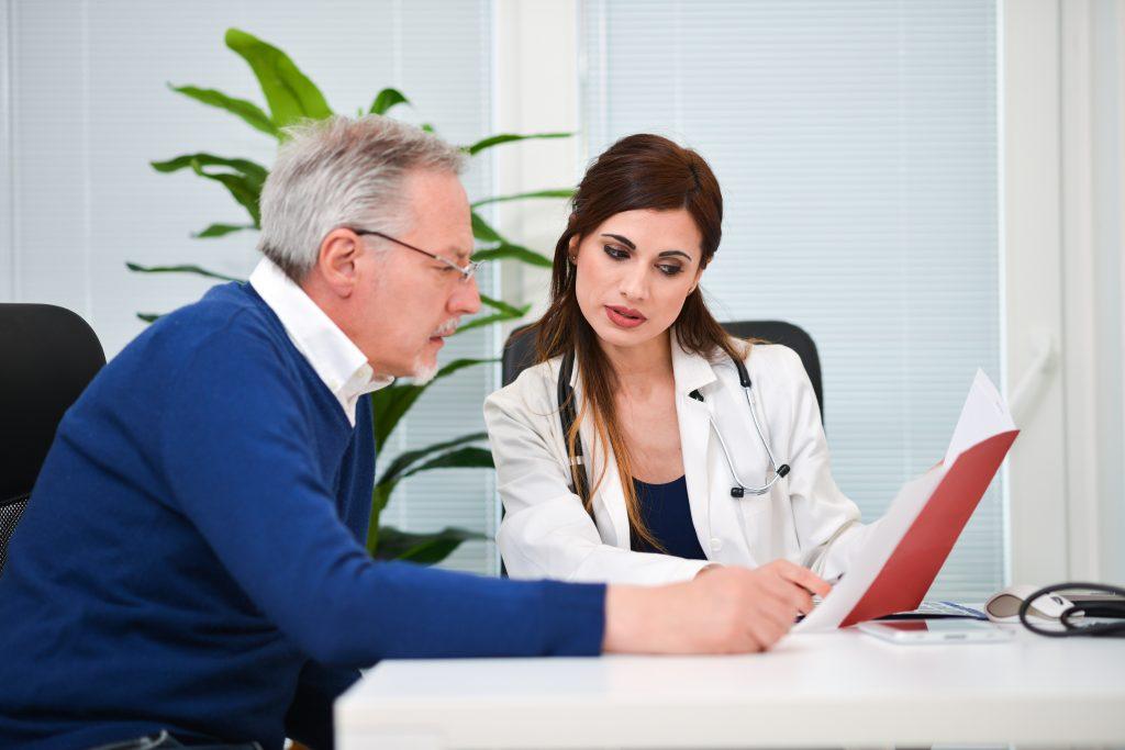 Elderly man discusses nursing home brochure with doctor